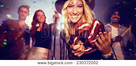 Flying colors against portrait of woman with musicians playing tambourine at nightclub