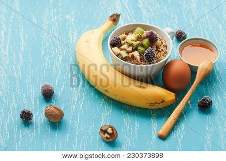 Oat Flakes With Cherry, Kiwi, Blackberry, Egg, Walnut And Honey In Small Cup. 45 Degrees View Of Hea