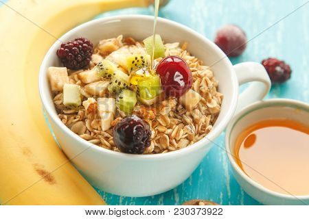Cup Of Oat Flakes With Cherry, Kiwi, Blackberry, Egg, Walnut And Honey In Small Cup. 45 Degrees View