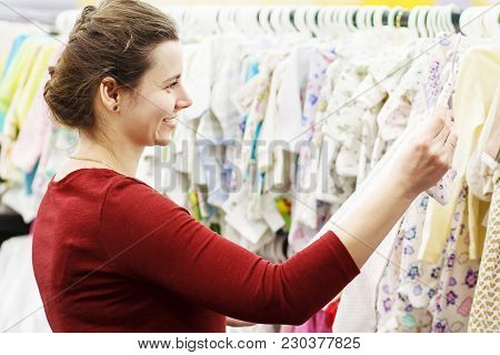 A Young Mother Chooses Clothes For Her Baby In A Children's Store. The Girl Chooses Clothes In The M