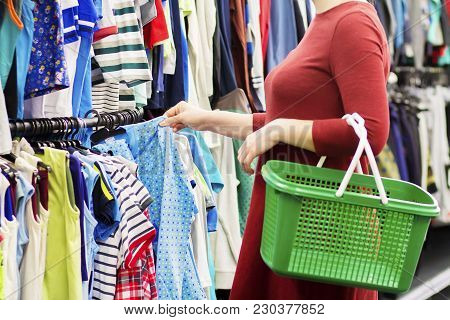 Girl With Shopping Basket Chooses Clothes In Supermarket. Buy Clothes In The Supermarket Concept. Sh