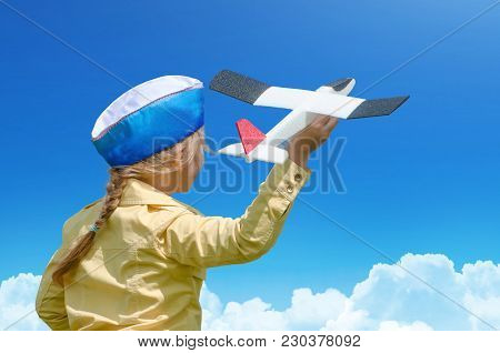 Happy Baby Girl Kid In A Cap Playing With Toy Airplane Against Blue Summer Sky Background. Concept -