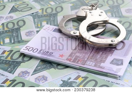 Police Handcuffs Lies On A Set Of Green Monetary Denominations Of 100 Euros. A Lot Of Money Forms An