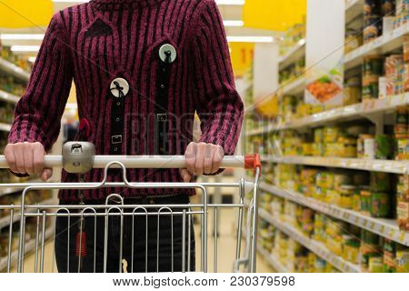 Young Woman Pushing Empty Shopping Cart In A Supermarket.