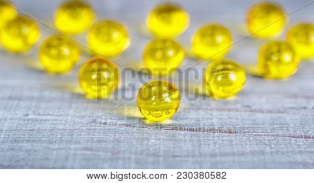 Shiny, Small Vitamin Capsules On Wooden Background