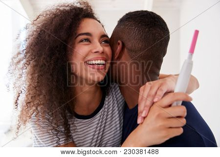 Couple Celebrating Positive Home Pregnancy Test Result