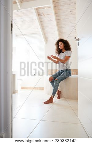 Concerned Woman In Bathroom Using Home Pregnancy Test