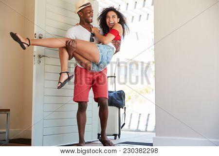 Man Carries Woman Over Threshold Of Honeymoon Rental