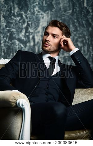 Portrait of a handsome man in an elegant suit sitting in an armchair on a grunge background. Studio shot.