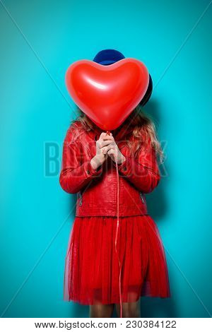 Pretty ten-year-old girl holding heart shaped balloon over blue background. First love. Valentine's Day.