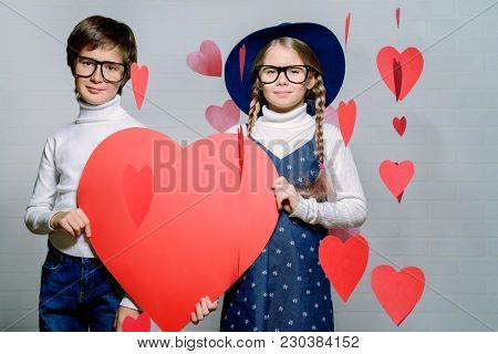Happy pre-teen boy and girl holding big red heart. Friendship. First love. Valentine's Day.