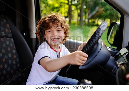 Baby Boy With Curly Red Hair Sitting At The Wheel Of A Car. Smiling Baby Driving A Car