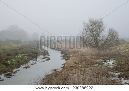 Cold Misty Winter Landscape Over Stream In English Countryside