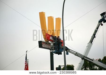 Lynwood California 3/9/2018: Workmen remove a McDonalds Restaurant sign with the M turned upside down for International Women's Day and replace it with the traditional sign.