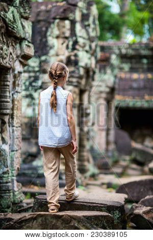 Little girl at ancient Preah Khan temple in Angkor Archaeological area in Cambodia