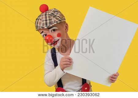Funny Child Clown Peeks Out Blank White Paper. Cute Little Boy Clown In Makeup, Red Nose. Little Che