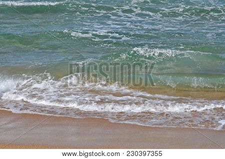 Small Waves Breaking At The Shoreline With Wet Sand.
