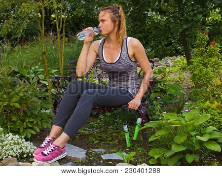 Young Woman With Jump Rope Sit On The Bench In A Garden And Drink A Clean Water