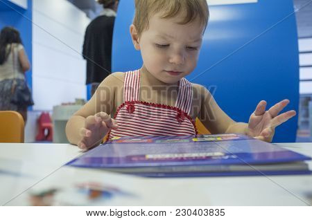 Adorable 2 Years Boy Browsing Stories At Library. Discovering The Book At His First Visit At Prescho