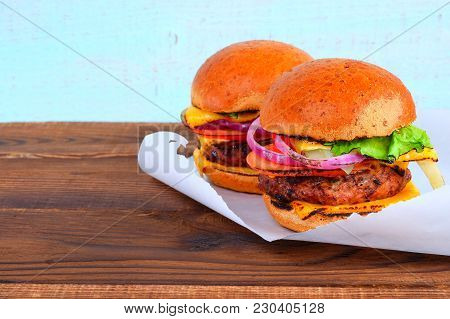 Two Tasty Hamburgers With Beef. Two Burgers Are Removed On A Snow-white Napkin On A Wooden Surface.