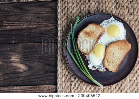 A Scrambled Eggs On A Plate. Plate With Scrambled Eggs, Toasted Bread And Onions Is Half On The Wood