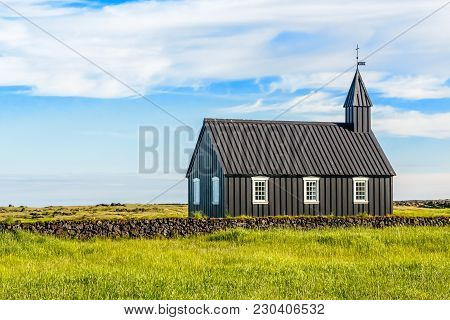 Budakirkja Black Painted Lutheran Church Erected In 1847 With Blue Sky And Clouds In The Background,