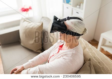 technology, augmented reality, entertainment and people concept - senior woman with virtual headset or 3d glasses at home