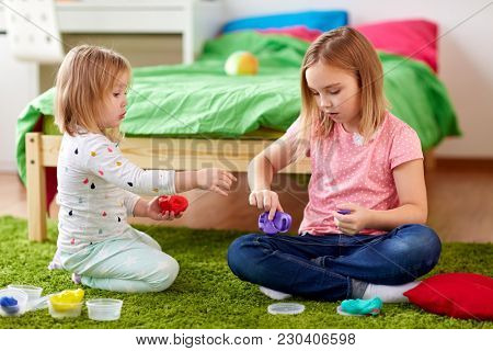 childhood, leisure and people concept - girls or sisters with modelling clay or slimes at home