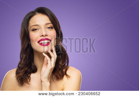 beauty, make up and people concept - happy smiling young woman with berry lipstick posing over ultra violet background