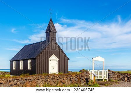 Budakirkja Black Painted Lutheran Parish Erected In 1847 With Blue Sky And Clouds In The Background,
