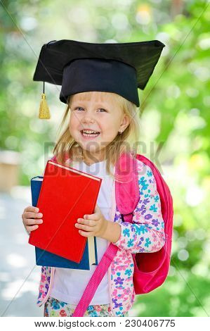 Little School Blonde Girl In School Classroom With Backpack And Books Posing