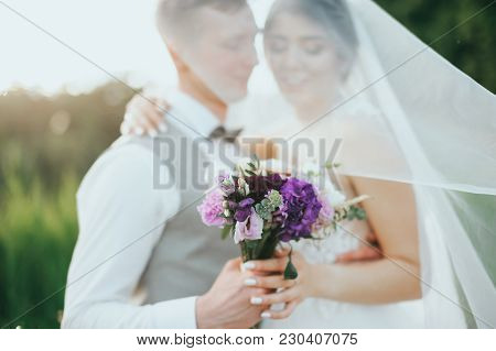 Wedding Couple Posing On Sunset At Wedding Day. Bride And Groom In Love. Bridal Veil