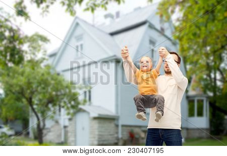 family, childhood, fatherhood, leisure and people concept - happy father and little son playing and having fun over house background