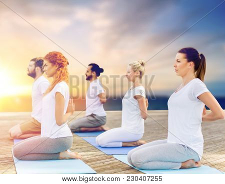 fitness and healthy lifestyle concept - group of people doing yoga reverse prayer pose on wooden pier over sea background