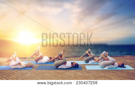 fitness, yoga and healthy lifestyle concept - group of people doing half ankle to knee supine pose outdoors on wooden pier over sea background