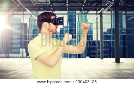 3d technology, virtual reality, entertainment and people concept - young man with virtual reality headset playing game and fighting over empty industrial room and city panorama background