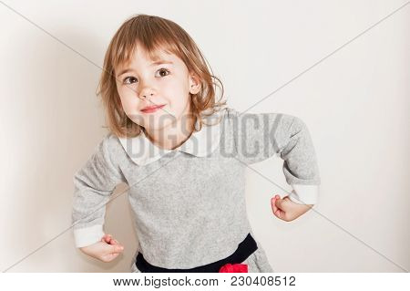 Portrait Of Grimacing Little Baby Girl On Light Background