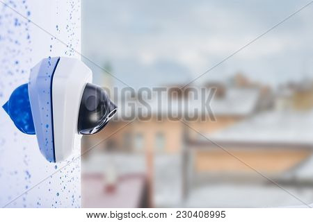 Ip Camera On The Wet Wall, Blurred City Background, Space For Text. Concept - Technology And Securit