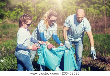 volunteering, charity, cleaning, people and ecology concept - group of happy family volunteers with garbage bags cleaning area in park