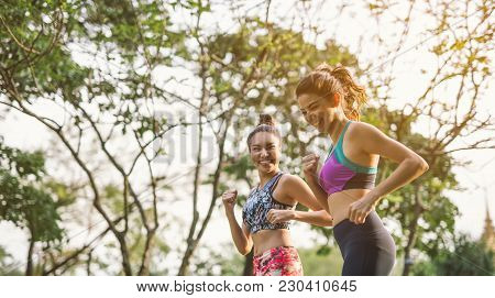 Two athletic woman running outdoors. Action and healthy lifestyle concept.Jogging run in park
