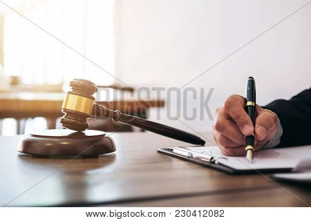 Gavel On Wooden Table And Lawyer Or Judge Working With Agreement In Courtroom Theme, Justice And Law