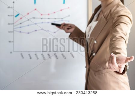 Business Woman Leader Making Presentation With Her Colleagues, Pointing To The Graph On Board And Bu