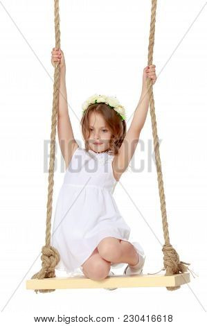 Adorable Little Girl Swinging On A Swing. She Is Happy To Have Fun And Show How She Can Do It. The C