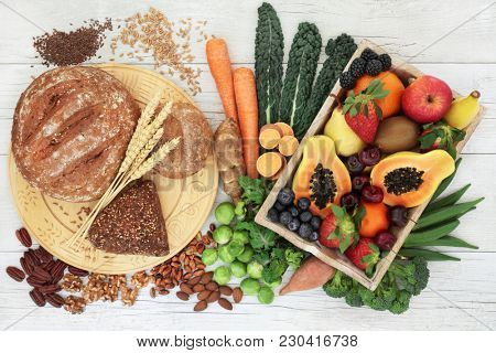 High fibre healthy food concept with wholegrain bread and rolls, nuts, seeds, fruit, vegetables and grains with foods high in antioxidants, omega 3 fatty acids, anthocyanins and vitamins.  Top view.