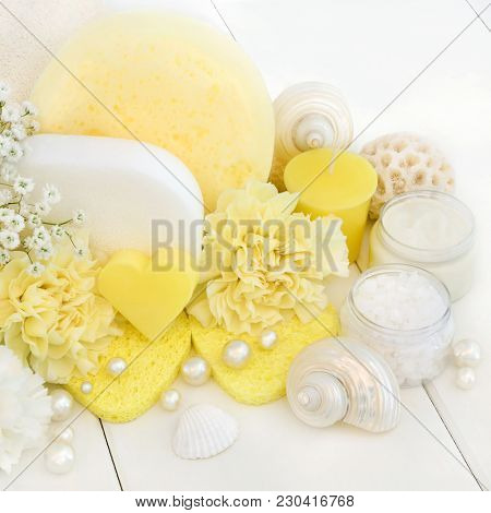 Spa and bathroom beauty treatment accessories with moisturising cream, ex foliating salt, heart shaped soap, sponges, yellow carnation flowers with decorative seashells and pearls.