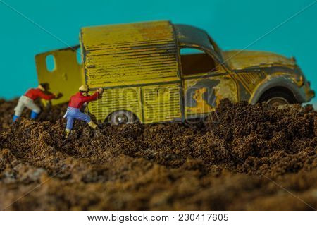 Old Car Bogged Down In A Ground, Toy Yellow Car On The Blue Background