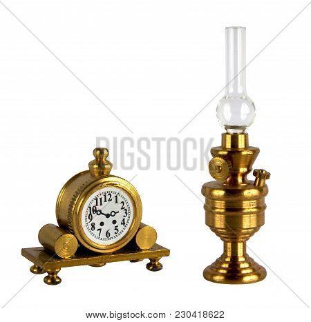 Brass Figurines Or Miniature Of Vintage Kerosene Lamp And Mantel Clock Isolated On White Background