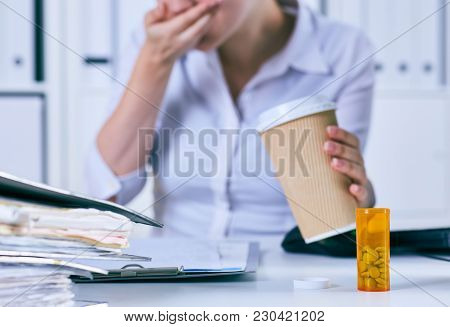 Sick Businesswoman Holding Cup Of Coffee And Medical Pill At Workplace, Suffering From Migraine Head