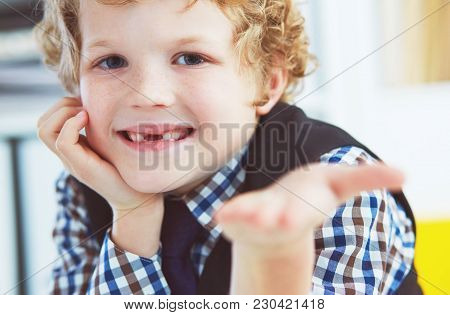 Litle Caucasian Boy Holds A Dropped Milk Tooth Between His Fingers And Laughs.