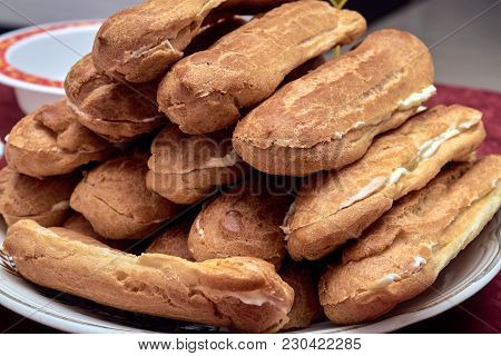 On The Plate There Are Several Home-made Eclairs. Eclairs Cut In Half. Stuffed With Vanilla Butter C